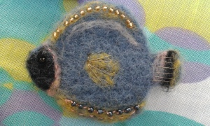 Blue needle felted fish brooch with bead detail.