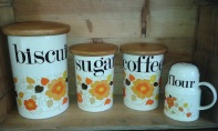 Biscuit, sugar & coffee cannisters in cream with orange flower decoration & wooden lids & matching flour shaker.