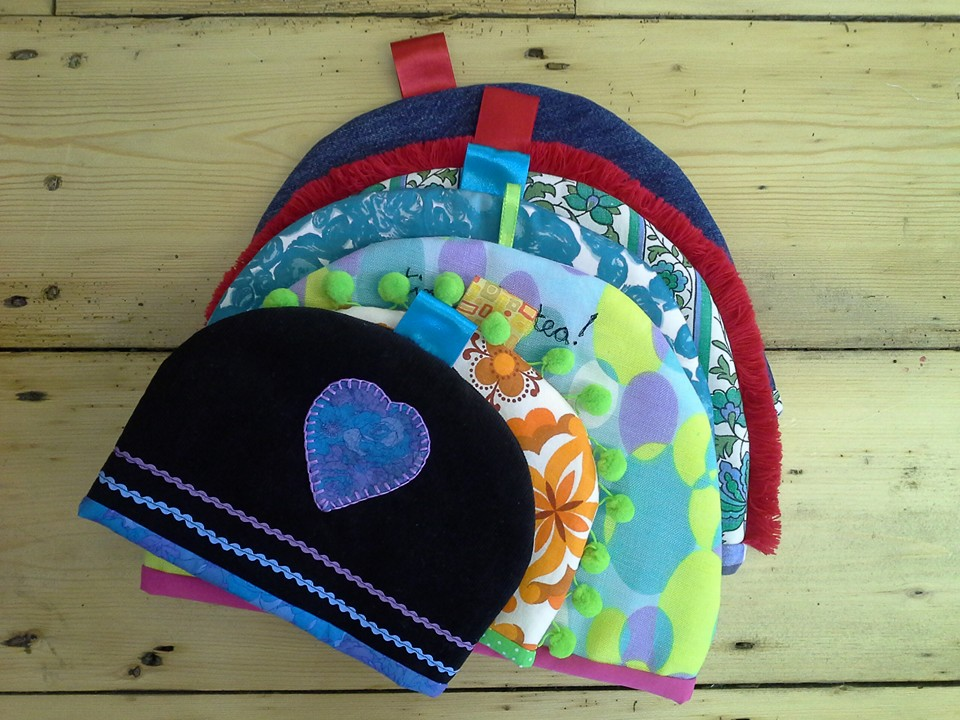 A selection of handmade teacozies n bright retro fabrics made at Tuftydawn Designs