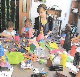 Children with painting and collage materials around a table at the Tuftydawn Designs studio.