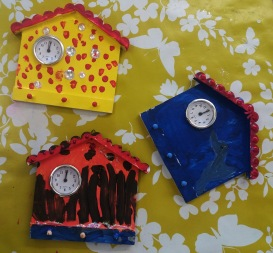 Three house shaped wooden clocks painted in bright colours by children at Tuftydawn Designs.