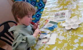Boy creating a collage picture of a tree using newspaper at Tuftydawn Designs.