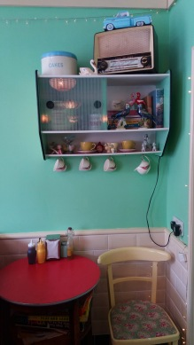 Retro 1950s display unit, ornaments, table and chairs at Delphine's Diner, Aldeburgh.