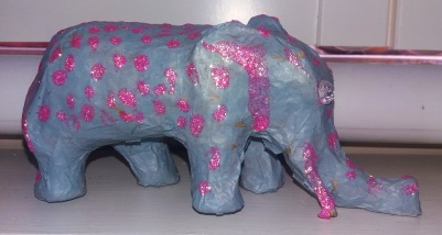 A grey decoupage paper mache elephant with pink glitter glue decoration.