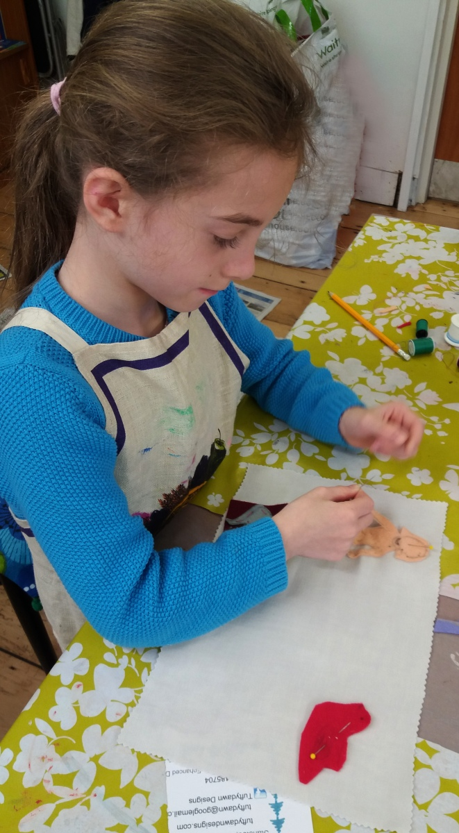 Young girl sewing felt shapes onto a fabric background at Tuftydawn Designs studio.