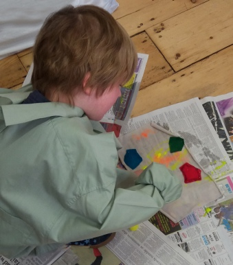 Young boy spraying fabric paint onto fabric with felt shapes sewn on to it at the Tuftydawn Designs studio.