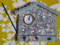 Decoupaged wooden clock and key tidy in the shape of a house.