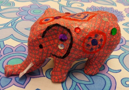 Decoupage elephant with pink flowery paper and sequins.