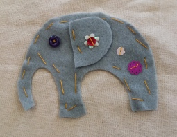 Grey felt elephant sewn onto cream fabric with sequins and a button made at the Tuftydawn Design studio.