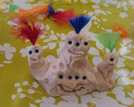 Pale pink playdough alien with three heads and feathers.