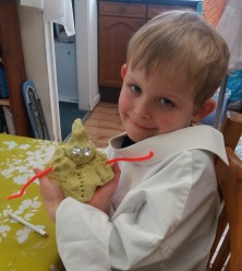 Young boy holding a playdough model of a snowman made at Tuftydawn Designs.