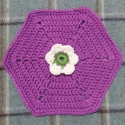 Crocheted Frida's Flowers Hexagon in purple, cream and green yarn.