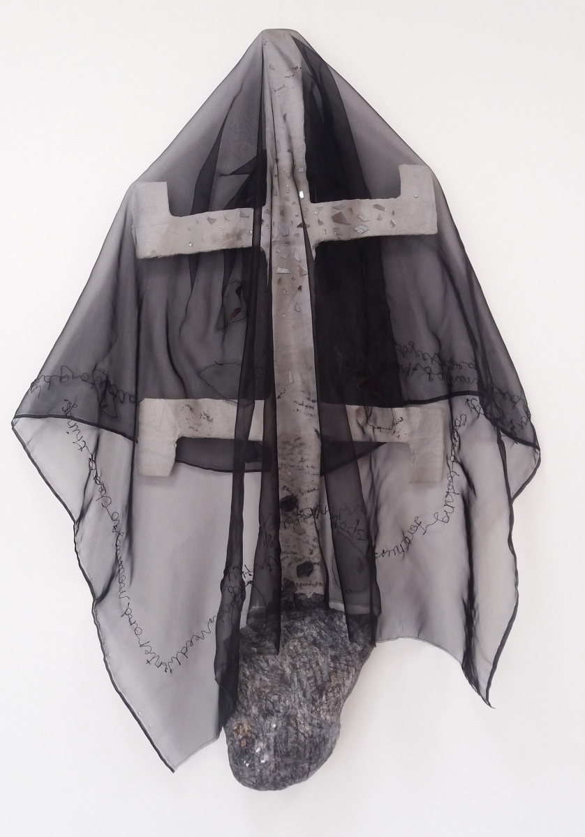 Kanaga mask covered with a black voile cloth embroidered with text & pockets of seeds.