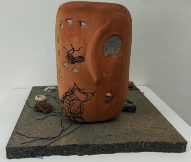 Wooden mask with inlaid threads, silver leaf, threads leading to shells and stones, mounted on a marble base.