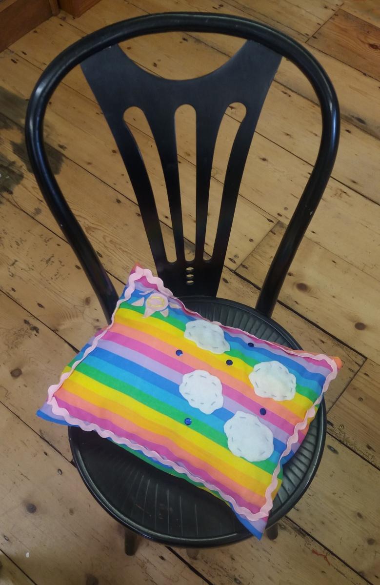 Rainbow striped cushion with pink ric rac border, hite felt clouds, sequin raindropsand a pink felt sun made at the Tuftydawn Designs studio.