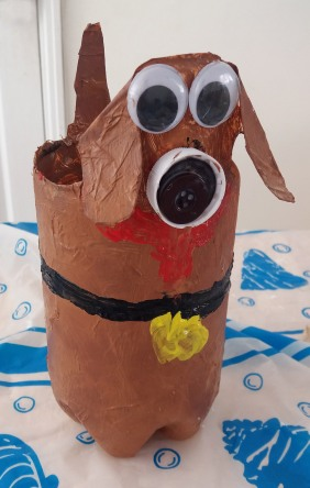 Tall brown dog with big googly eyes made from a plastic bottle made with Tuftydawn Designs.