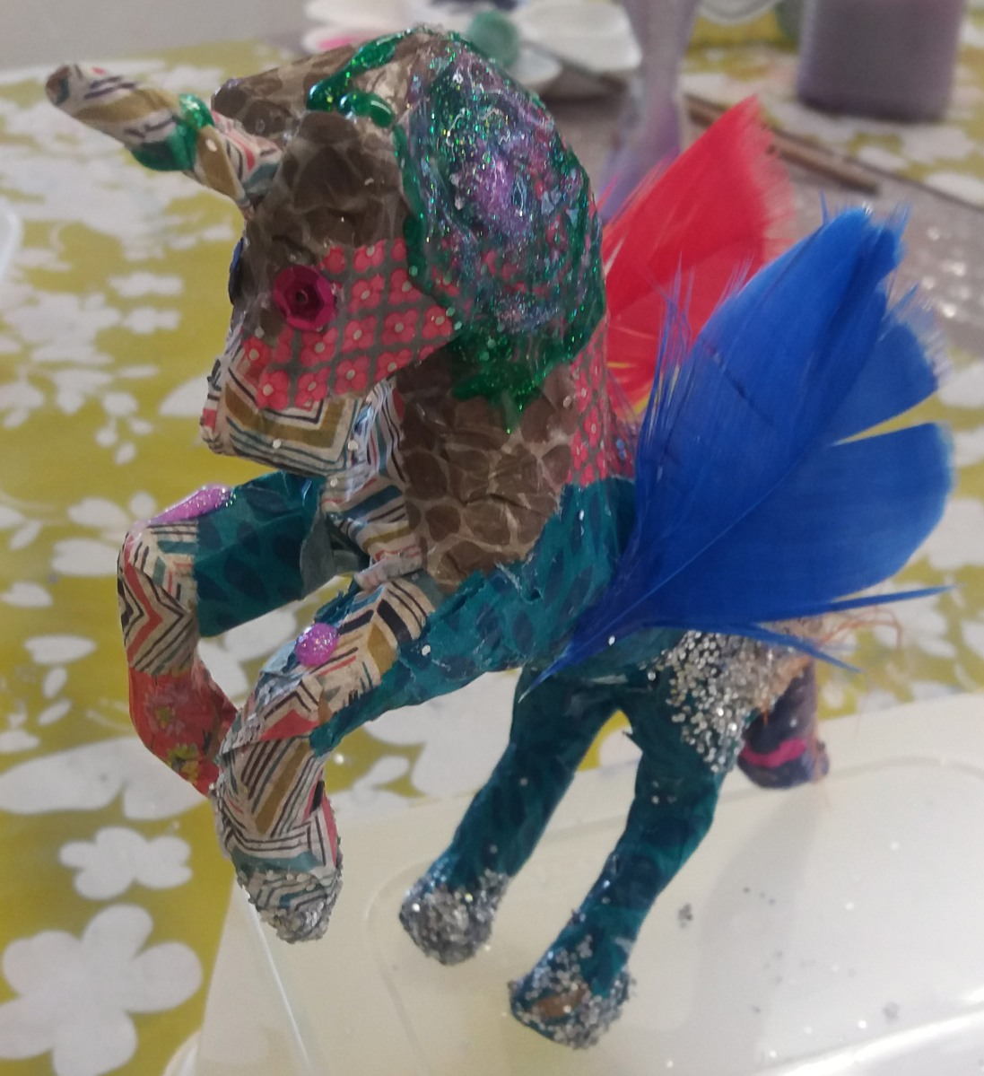 Decoupage unicorn with blue & red feathers, glitter & sequins made at the Tuftydawn Designs studio.