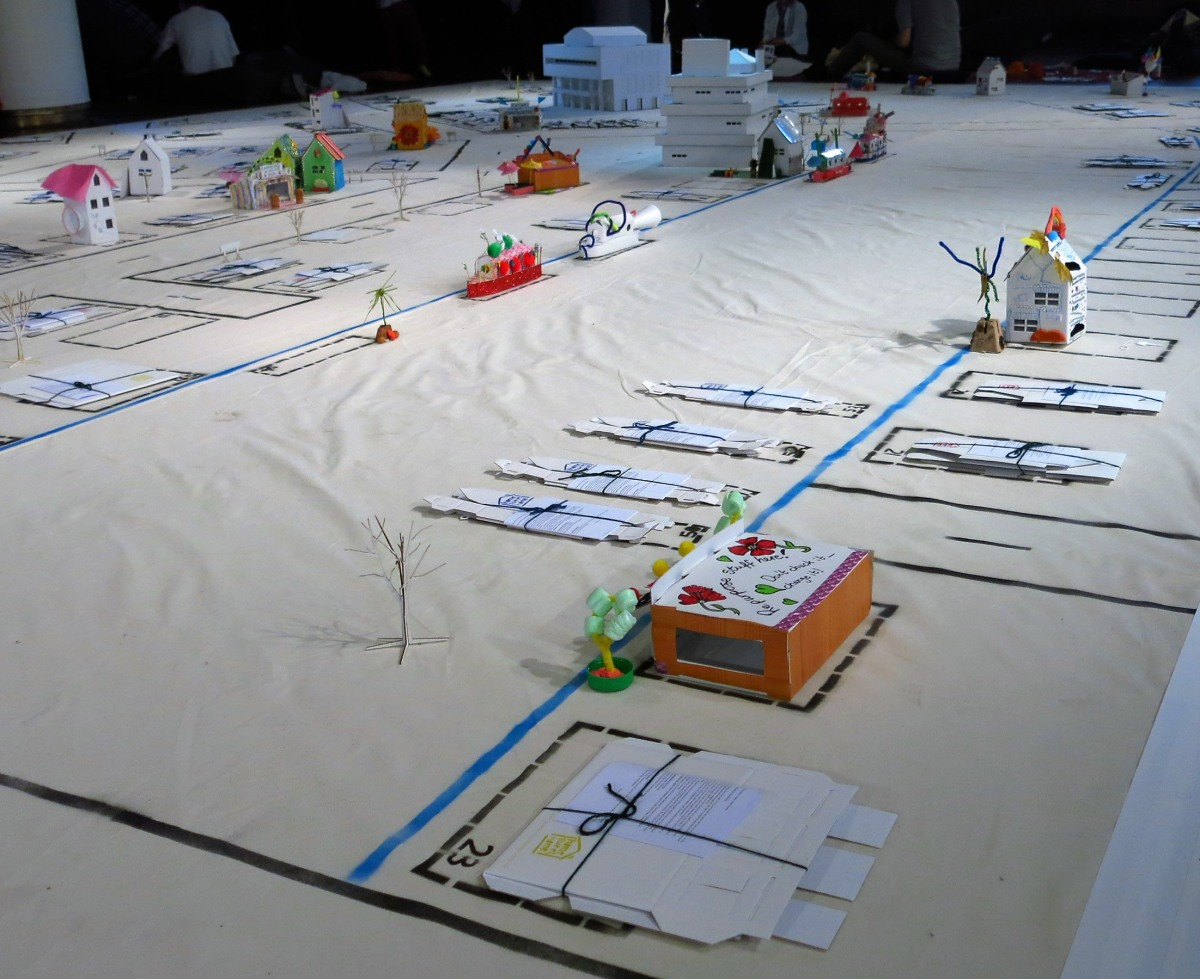 Cream canvas flooring with cardboard buildings laid out along the streets.
