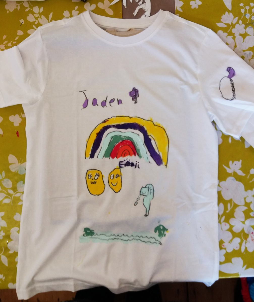 White T shirt with a rainbow and emoji painted on made at the Tuftydawn Design studio.