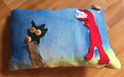Cushion with a red felt dinosaur, palm tree on a blue background made at Tuftydawn Designs studio
