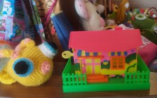 Neon pink, green & yellow plastic money box in the shape of a house.