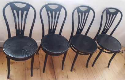 Four black wooden bistro style chairs.
