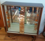 Glass & mirror cocktail cabinet with sliding doors & orange & gold flower details.
