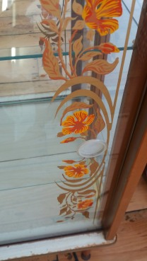 Cocktail cabinet detai with gold & orange flowers on glass door.