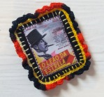Brooch with a textile mini picture in the middle & black, red & yellow crochet edging.