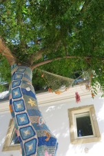 Photo of a tree with crocheted sea themed elements around the trunk.