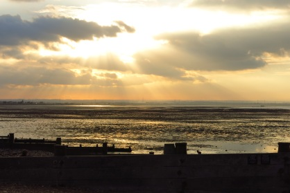 Sunset over Whitstable with rays of light flooding through the clouds.
