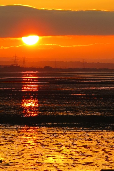 Very bright orange sunset over Whitstable beach.