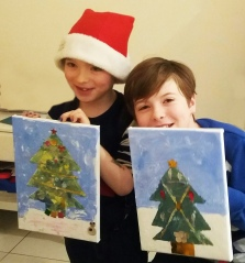 Two boys holding up Christmas tree paintings made with Tuftydawn Designs.