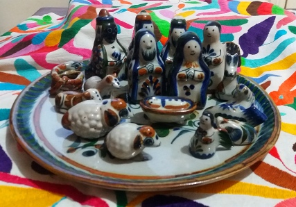 Group of Mexican Nativity figures made of glazed china, with a bright Mexican cloth background.