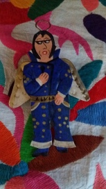 Painted tin decoration of Elvis in a blue and gold jumpsuit with a halo and angel wings.