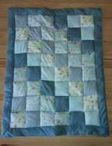 A square block baby's quilt made with blue toned cotton fabrics made by Tuftydawn Designs.