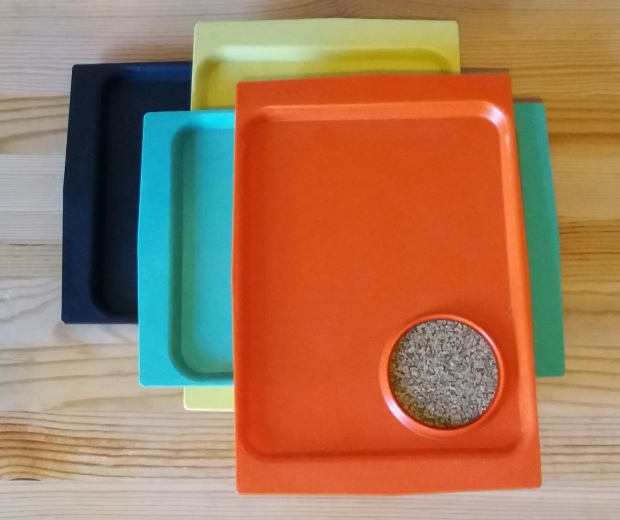 Stack of four acca trays in orange, green, yellow and black.