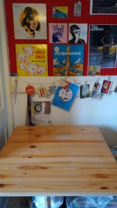 An empty pine table in front of a red and white wall with record covers, button swatches, postcards and concert tickets decorating it.