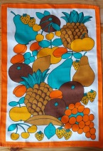 A tea towel in bright oranges & greens of a pile of exotic fruit.