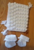 Puff stitch baby hat and booties in white yarn.